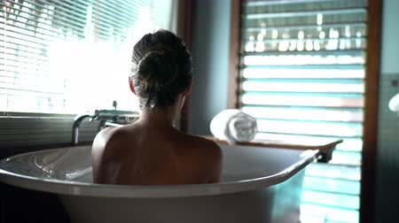 hotel suite : bath woman relaxing in hot bathtub in hotel resort suite room enjoying pampering spa moment lifestyle.
