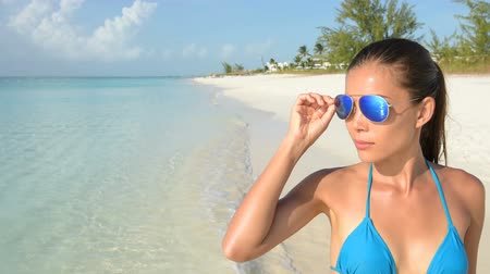 letec : Sunglasses - Beach bikini woman wearing fashion eye wear. Young female adult model with trendy blue mirrored aviator mirror sunglasses and turquoise swimwear top looking at the ocean.