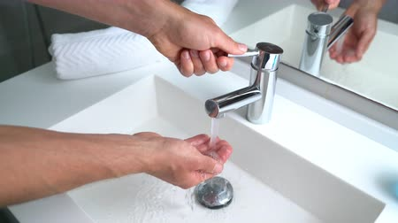 lavagem : Man washing hands in bathroom sink at home checking temperature touching running water with hand. Closeup on fingers under hot water out of a faucet of a sink.