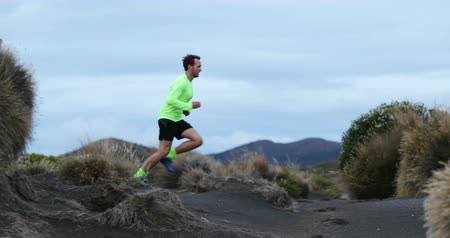 cross country : Trail runner man running in mountain nature landscape enjoying training run workout. 59.94 FPS slow motion.