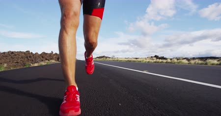 bioscoop : Running shoes on male triathlete runner - close up of feet running on road. Man jogging outside exercising training for triathlon ironman. REAL TIME on RED Cinema Camera. Stockvideo