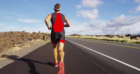 kimerül : Running runner in Triathlon - Triathlete man running in triathlon suit in ironman race. Male runner exercising on Big Island Hawaii. REAL TIME STEADY TRACKING SHOT on RED Cineama Camera. Stock mozgókép
