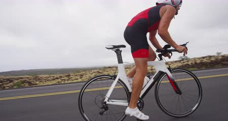 fegyelem : Cycling Triathlon man - male triathlete biking on triathlon bike on road. Fit cyclist on professional triathlon bicycle wearing tri suit time trail helmet training for ironman. From Big Island, Hawaii Stock mozgókép