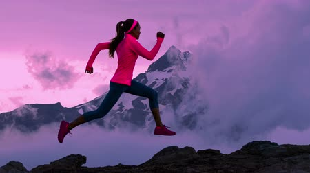 sprintel : CINEMAGRAPH - seamless loop. Trail runner athlete silhouette running in mountain summit background clouds and peaks. Woman on run training outdoors active fit lifestyle. Looping Motion photo image.