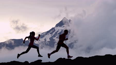 kaland : CINEMAGRAPH - seamless loop video. Running people athletes silhouette trail running in mountain summit background. Man and woman on run training outdoors active fit lifestyle. Looping Motion photo.