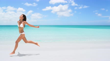 gif : CINEMAGRAPH - seamless loop: Happy woman running on the beach on travel vacation holidays. Image full of aspiration and joy with Caucasian  Asian Chinese bikini model having fun. Looping Motion photo