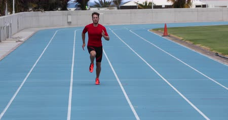 stopa : Sprinter man running sprint training on athletics track and field stadium fast at high speed. Male athlete runner in intense sprint exercise. Run sport concept. REAL TIME.
