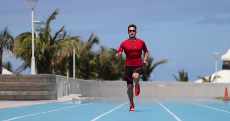 stopa : Sprinting man sprinter running sprint training on athletics track and field stadium fast at high speed. Male athlete runner in intense sprint exercise. Run sport concept. REAL TIME.