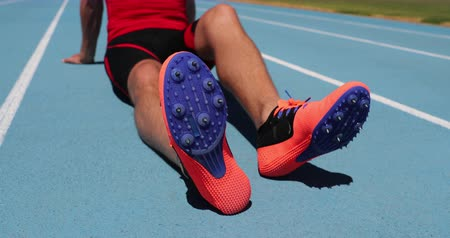 stopa : Athlete sprinter relaxing after run on athletics running track and field stadium. Close up of spike running shoes on man track runner resting after sprint training outdoors. Fitness and sports. Dostupné videozáznamy