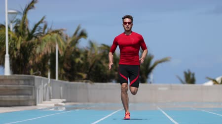 pace : Sprinter man running sprint training on athletics track and field stadium fast at high speed. Male athlete runner in intense sprint exercise. Run sport concept. SLOW MOTION 59.94 FPS.