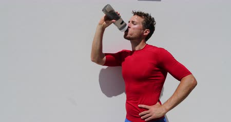 sportowiec : Tired exhausted dehydrated man runner drinking water bottle after workout. Running person taking a break after run. Fitness athlete breathing catching breath in summer outdoor training.