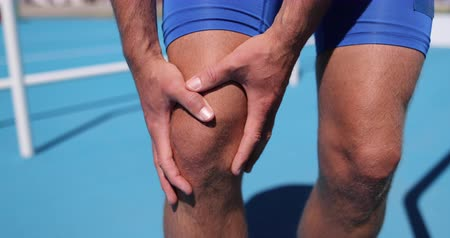 ferido : Injuries - sports running knee injury on man. Male runner with pain, maybe from sprain knee or arthritis. Close up of legs, muscle and knee outdoors.