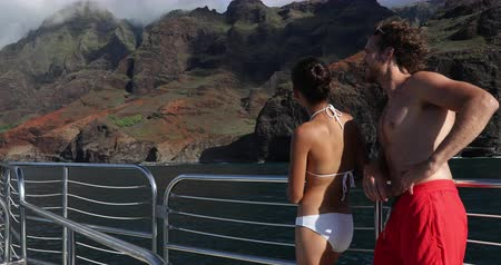 havaiano : Couple Hawaii cruise ship boat. Tourists People on Na Pali Coast of Kauai, Hawaii. Sunset cruise leisure tourist activity in NaPali. Couple looking at famous Hawaiian travel destination. Hawaii Vídeos