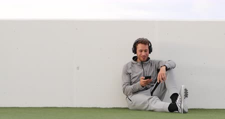melegítőben : Man listening to music mobile phone app wearing headphones sitting outdoors on grass. Healthy lifestyle sport athlete using smartphone on jogging break outdoors. Real time.