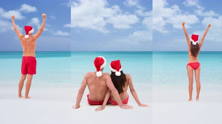 emelt : CINEMAGRAPH - 3 VERTICAL SEAMLESS LOOP videos: Christmas couple wearing santa hat. Happy cheering arms raised winning and sitting on white sand beach travel destination winter holidays.