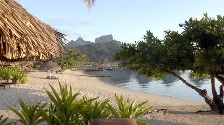 bungaló : SEAMLESS LOOP VIDEO: Beach on Bora Bora vacation paradise island with overwater bungalows resort hotel and beach hut in coral reef lagoon ocean and beach. Mount Otemanu, Bora Bora, Tahiti.