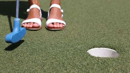 golfové hřiště : Mini golf or Miniature golf, also known as minigolf, mini-putt, crazy  golf. - woman putting with golf club ball in hole.