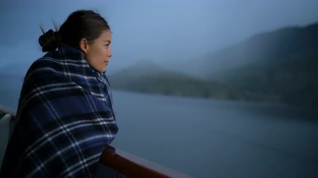 スイート : Cruise ship passenger on Alaska travel vacation enjoying scenery at dusk on suite balcony deck with wool throw in cold weather. Asian tourist woman relaxing on summer holiday cruising adventure. 動画素材