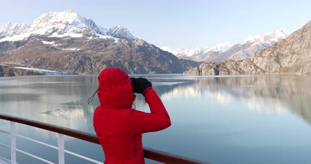 glacier national park : Alaska Glacier Bay cruise ship passenger looking at Alaskan mountains with binoculars exploring Glacier Bay National Park, USA. Woman on travel Inside Passage enjoying view. Vacation adventure.