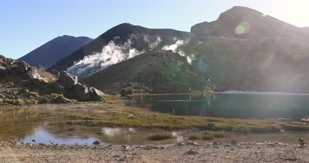 emerald green : New Zealand. Tongariro Crater Summit and Emerald Lakes of Tongariro Alpine Crossing. Active volcano with smoke and fumes on hiking tramping track on North Island, New Zealand. Stock Footage