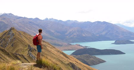 vulkán : Travel hiker looking at view of mountain lake nature landscape on New Zealand on famous Wanaka hike to Roys Peak. Hiking man enjoying amazing nature on New Zealand. 59.94 FPS SLOW MOTION.