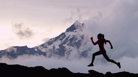 gif : CINEMAGRAPH - SEAMLESS LOOP. Trail runner athlete silhouette running in mountain summit background clouds and peaks. Woman on run training outdoors active fit lifestyle. Looping Motion photo image