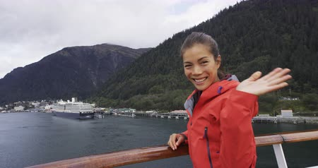 аляскинским : Cruise ship passenger in Alaska city of Ketchikan waving hands saying hello looking at camera while sailing Inside Passage. Ketchikan is a famous Alaska cruise ship destination for travel sightseeing.