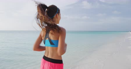 sportowiec : Exercising young woman runner jogging and running on beach happy living healthy aspirational fitness lifestyle. Sporty young Asian Caucasian female in sportswear. REAL TIME STEADICAM RED Camera