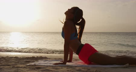 visszavonulás : Yoga fitness woman stretching abdominals practicing morning sequence doing upward facing dog. Fit fitness girl stretching on beach at sunrise. Beautiful multiracial female model.