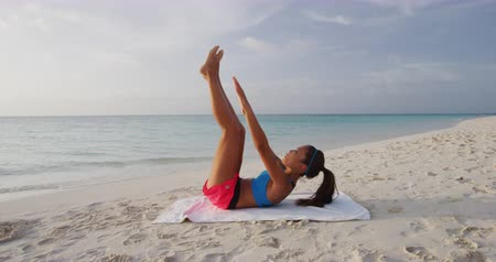 toes : Fitness woman training working out on beach outdoors doing toe touch crunches. Girl on beach training obliques stomach muscles doing core body training. Fit girl exercising doing abs exercise.