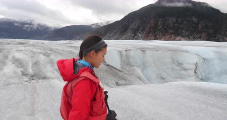 személyszállító hajó : Woman walking on glacier in Alaska on glacier helicopter tour from Skagway. Tourist visiting Chilkat glacier on tour cruise ship shore excursion. 59.94 FPS SLOW MOTION. Stock mozgókép