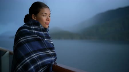 аляскинским : Cruise ship passenger on Alaska travel vacation enjoying scenery at dusk on suite balcony deck with wool throw in cold weather. Asian tourist woman relaxing on summer holiday cruising adventure. Стоковые видеозаписи
