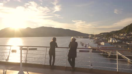 аляскинским : Cruise ship passengers in Alaska city of Ketchikan standing on cruise ship deck talking sailing Inside Passage. Ketchikan is a famous Alaska cruise ship destination for tourist travel sightseeing.