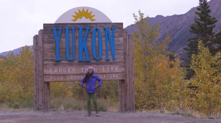 canadense : Yukon territory welcome sign - happy tourist woman in Canadian territories by tourist attraction sign. Alaska cruise travel autumn holiday. Stock Footage