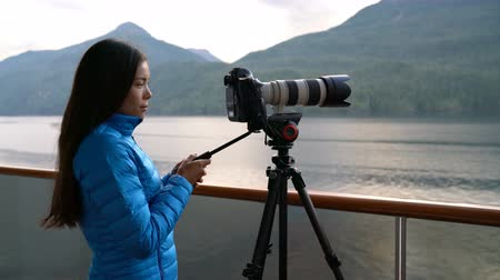 кит : Travel photographer with professional telephoto lens camera on tripod shooting wildlife in Alaska, USA. Scenic cruising inside passage cruise tourist vacation adventure. Woman taking photo picture.