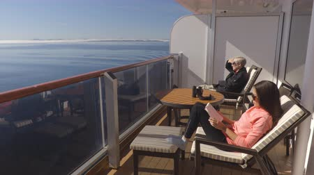 аляскинским : Cruise ship passengers in Alaska on cruise ship travel in the Inside Passage. Woman tourists relaxing and reading book looking at landscape with binoculars. Alaska cruise ship destination sightseeing. Стоковые видеозаписи
