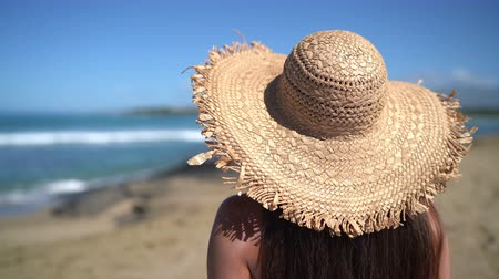 curacao : Woman relaxing on beach wearing sun hat fashion summer accessory. View from back of woman enjoying summer holidays. Stock Footage
