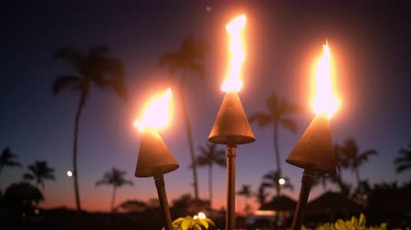 Оаху : Hawaii sunset with fire torches. Hawaiian icon, lights burning at dusk at beach resort or restaurants for outdoor lighting and decoration, cozy atmosphere.