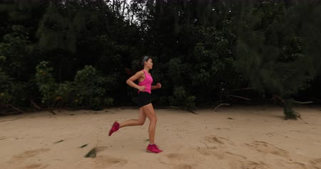 Észak amerika : Running woman on beach by forest tree training and working out Trail runner living healthy active outdoor lifestyle training. Female trail runner, 59.94 FPS. North Shore, Oahu, Hawaii, USA.