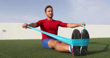 pull out : Fitness man training shoulders back and arms with resistance bands at outdoor gym. Body workout with equipment outside. Elastic rubber band accessory. SLOW MOTION 59.94 FPS. Stock Footage