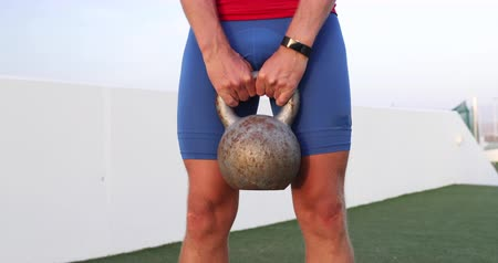obtížný : Fitness man lifting heavy kettlebell weight for legs workout. Cross training class in outdoor studio.