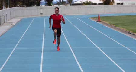 stopy : Running sprinter man in sprint training on athletics track and field stadium fast at high speed. Male athlete runner in intense sprint exercise. Run sport concept. 59.94 FPS slow motion. Dostupné videozáznamy