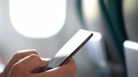 first class : Phone. Plane passenger man texting on mobile phone using in-flight onboard wifi internet on business travel trip holding cellphone. 5G technology device. Two people using phones in plane. Stock Footage
