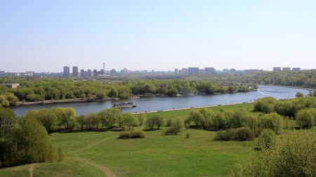 Nature, spring. View from the mountains to the river. On the river boat sails. In the distance a large city is visible. Landscape.