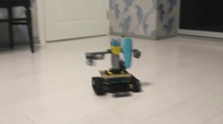 A robot made from a designer on the floor in the apartment. A small robot moves on the white floor.