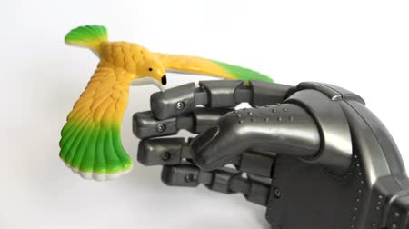 A little bird is sitting It is yellow, it is not alive, but it is rotates. Robot hand is a toy. The concept of love and kindness. Stock Footage