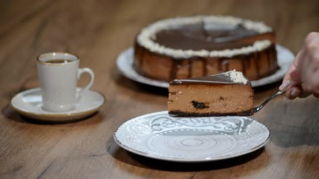 чизкейк : Putting a piece of chocolate cheesecake on a plate
