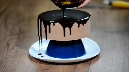 глазурь : Glaze chocolate cake. The confectioner glazes a cake and garnishes it with gold.