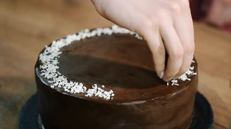fondán : Decorating chocolate coconut cake with coconut shavings.