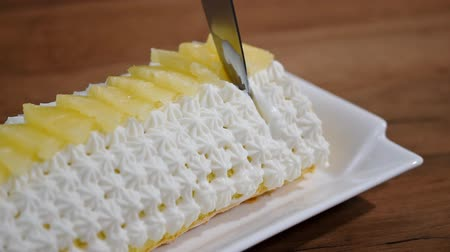 çırpılmış : Cutting a piece of pineapple roll cake. Stok Video
